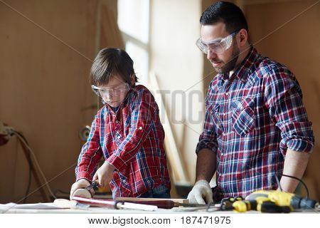 Father and son woodcrafting in workshop