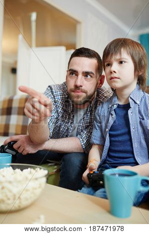 Father pointing at tv screen while gaming with his son at leisure