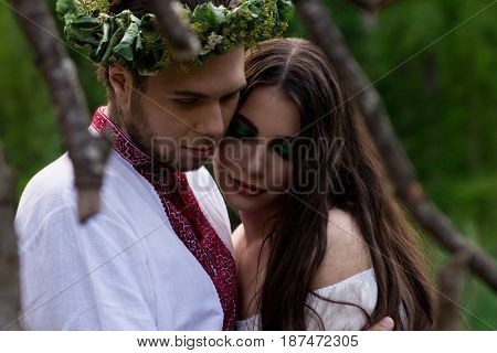 Guy hugs young beautiful girl at folk festival. Folk style. Close-up view