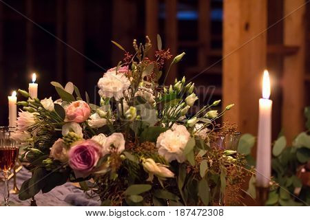 Laid Table By wedding banquet in a wooden barn. Candles and bouquet. Vintage Style.