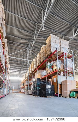Warehouse industrial and logistics companies. Long shelves with a variety of boxes and containers.
