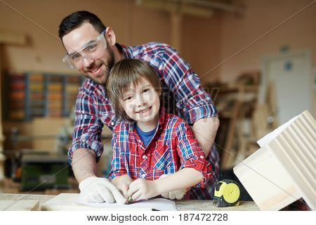 Happy man and boy working together in handcraft workshop
