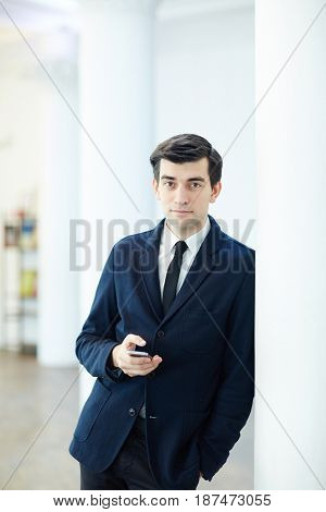 Business specialist with gadget looking at camera