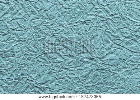 the old crumpled sheet of paper of pale turquoise color for the abstract textured background and for wallpaper