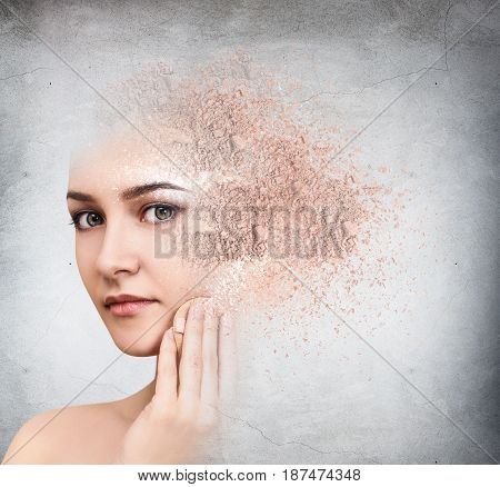 Woman face made from crumbly powder over gray wall background