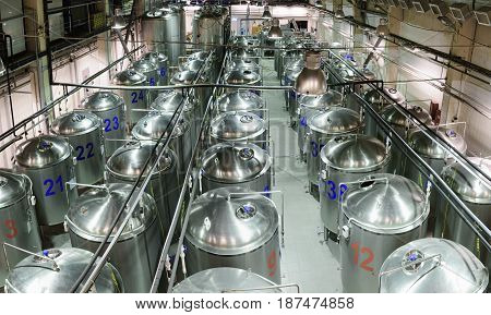 A factory for the production of beer. Long rows of glossy metal tanks.