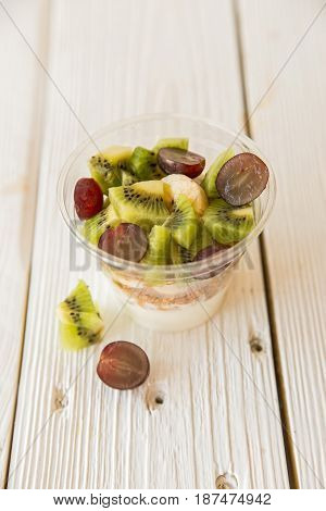 Close up home made youghurt with kiwi, banana and grapes and oat in plastic glass