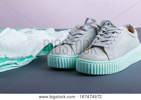 Close Up Of Grey And Mint Color Sneakers Near Pant. Female Outfit.