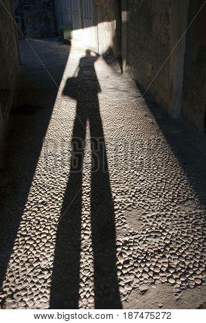 Trogir narrow street with long photographer shadow