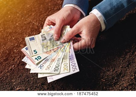 Bank loan for agricultural activity in euro banknotes businesswoman in elegant business suit with european currency cash money over fertile soil