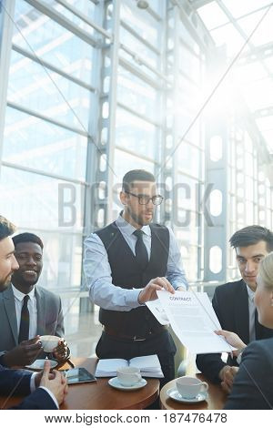 Business leader showing contract to his employees during discussion