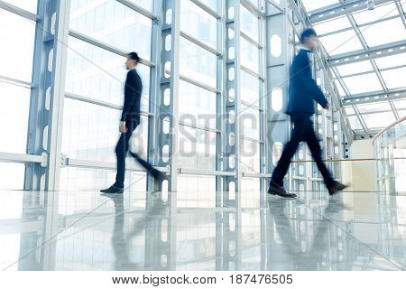 Blurred figures of modern businessmen hurrying for meetings