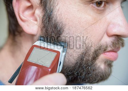 Close up image of handsome man with dark beard and electric shaver