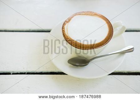Capuchino coffee on the white wood table.