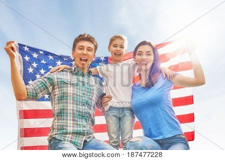 Patriotic holiday. Happy family, parents and daughter child girl with American flag outdoors on blue sky background. USA celebrate 4th of July.
