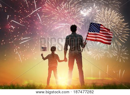 Patriotic holiday. Happy kid, cute little child girl and her father with American flag. USA celebrate 4th of July.