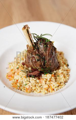 Braised lamb shank with herbs and bulgur cereal