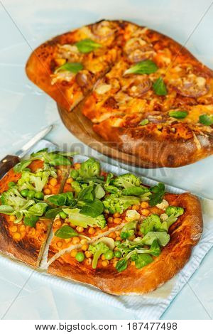 Vegan pizza and meat pizza. Pies with chickpeas and broccoli and meat pie.