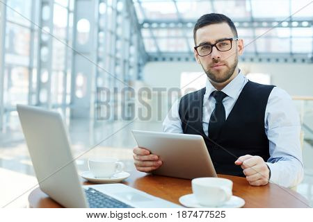 Serious leader with gadgets looking at camera by workplace