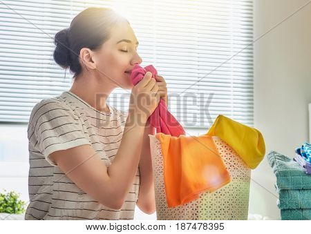 Beautiful young woman is smelling clean clothes and smiling while doing laundry at home.