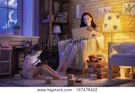 Happy loving family. Young mother and her daughter girl play in kids room. Funny mom and lovely child are having fun with laptop in the evening.