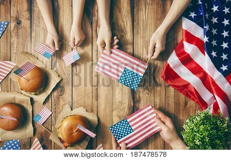 Patriotic holiday. Mother, father and child are doing burgers. Happy family are celebrate 4th of July. Top view with American flag in the room at home.