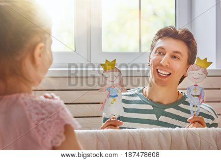 Happy loving family. Father and his daughter in kids room. Funny dad and lovely child having fun and playing performance in the puppet theater indoors. Prince and princess.