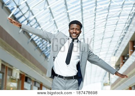 Joyful businessman in suit outstretching his arms