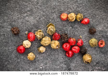 Peppercorns over black stone background. Top view.