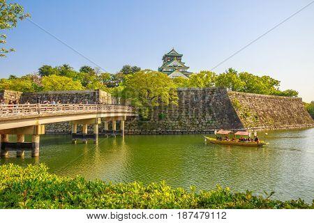 Osaka, Japan - April 30, 2017: Golden Wasen, a touristic boat, along the moat of Osaka Castle and Gokurakubashi Bridge, one of the best activities you can experience around Osaka Castle area.