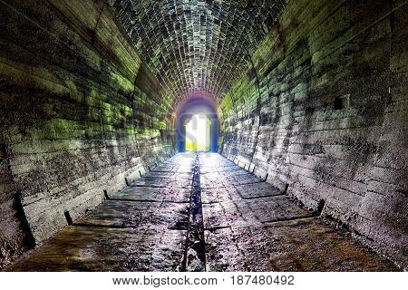 Long underground brick tunnel with light at end