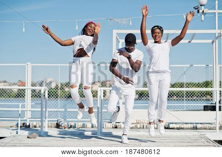 Three Stylish African American Friends, Wear On White Clothes At Pier On Beach. Street Fashion Of Yo