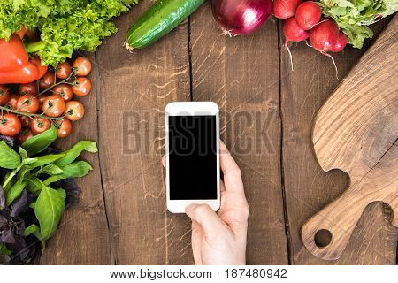 Top View Of Kitchen Table Full Of Various Vegetables And Human Hand Holding Smartphone With Blank Sc