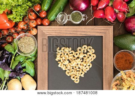 Cooking With Love Concept. Kitchen Table Full Of Vegetables, Spices And Green With Heart Sign Made F