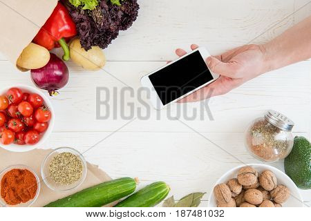 Overhead View Of Human Hand Holding Smartphone With Blank Screen Over Kitchen Table Full Of Organic