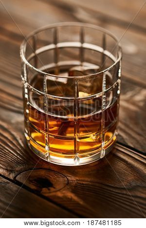 Glass of whiskey with ice cubes on rustic wooden table