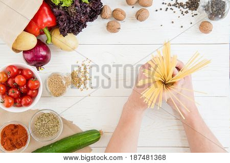 Close-up Partial View Of Hands Holding Raw Spaghetti And Fresh Vegetables With Spices On Wooden Tabl