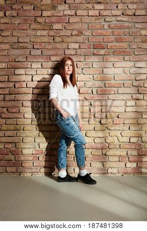 Casual young girl standing against brick wall hand in pocket.