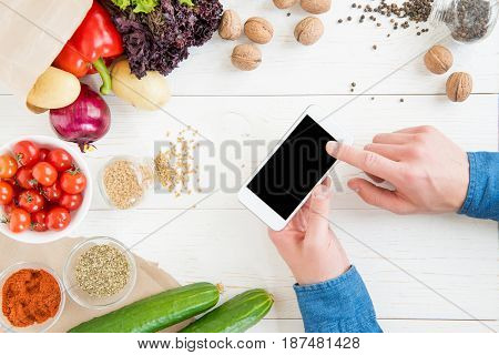 Close-up Partial View Of Person Using Smartphone With Blank Screen While Cooking And Fresh Ingredien