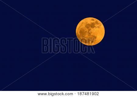 The big full moon in blue twilight sky.
