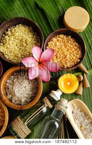 wooden bowl of color sea salt with , ,massage oil and frangipani, on banana leaf