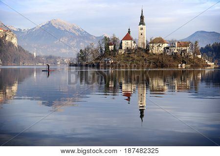 A man rowing away from the Church of the Assumption island in lake Bled Slovenia.