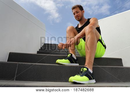 Runner tying running shoes laces getting ready to run on city stairs. Healthy active lifestyle man happy jogging motivation.