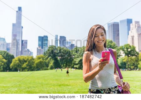 Happy Asian woman texting sms on mobile phone in New york City, NYC. Young girl walking in Central Park meadow in Manhattan.