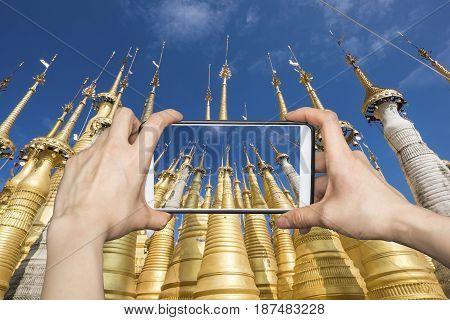 Tourist taking pagodas photo with smartphone in Indein village, Myanmar