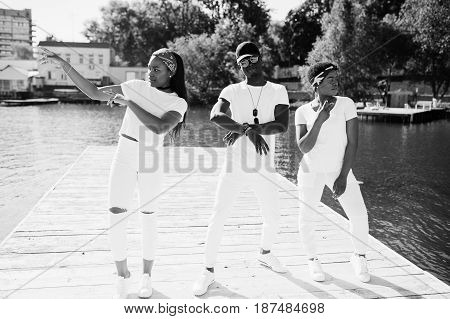 Three Stylish African American Friends, Wear On White Clothes At Pier On Beach Showing Dab. Street F