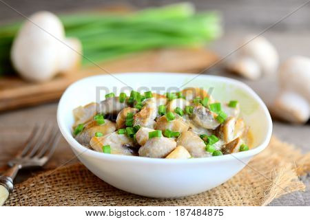 Fried mushrooms slices with sour cream sauce and fresh green onions in a bowl. Healthy vegetarian recipe. Homemade spicy mushrooms recipe. Fresh mushrooms, green onions, fork on old wooden table