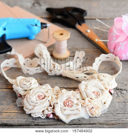 Casual floral fabric necklace, glue hot gun, scissors, thread, needle, felt on a vintage wooden table. Creating a flowers jewelry using vintage and recycled cotton fabrics, beads and felt