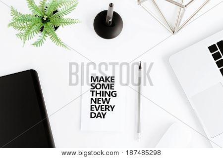 Flat Lay With Make Something New Everyday Motivational Quote On Modern Workplace With Wireless Devic