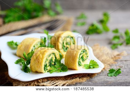 Homemade cheese and herbs stuffed omelet on a plate and vintage wooden table. Cut omelet with grated cheese and finely chopped herbs. Delicious and spicy breakfast omelette recipe. Rustic style